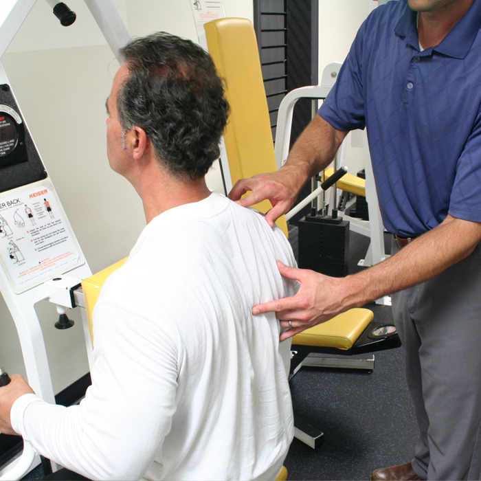 Dr Kauffman, owner of Thrive Milpitas, showing a patient how to properly use a workout machine for therapy.