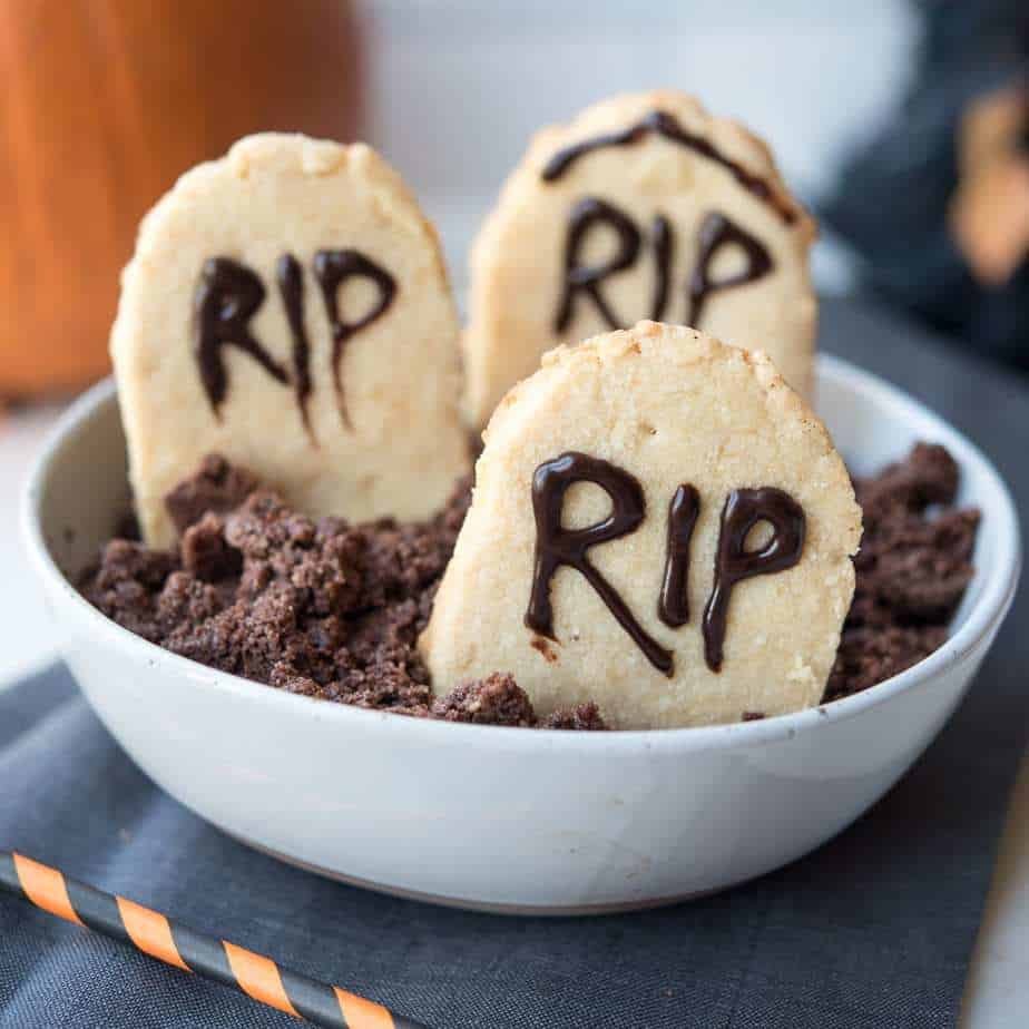 """Paleo Halloween Tombstone Cookies in gluten-free """"dirt"""" in a white bowl"""
