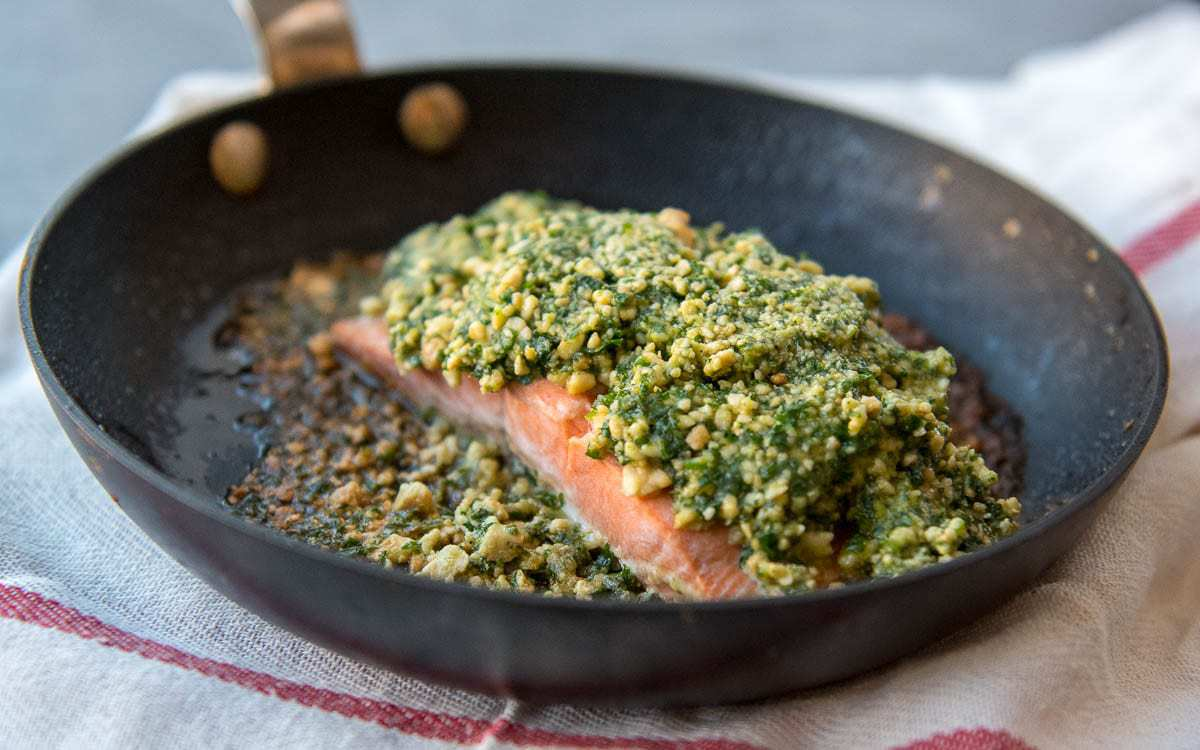 A pan with a salmon fillet, crusted with a cashew mixture