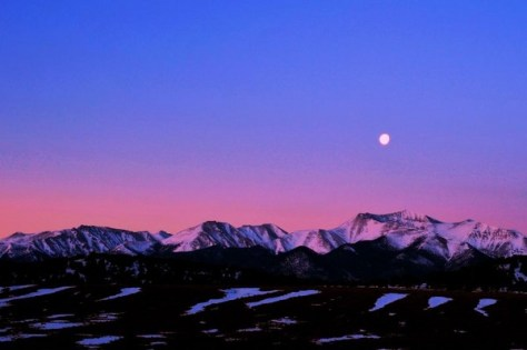 photo of the moon over the mountains, bathed in pink light