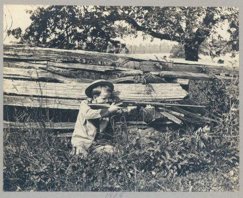 A Vintage photograph of a Young Boy Hunting Near a Woodpile