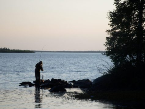 a photo of a fisherman with a small pike caught at sunset at silsby lake lodge in manitoba canada