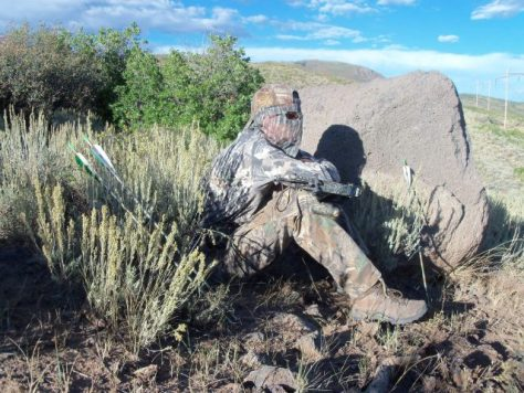 Bowhunter Pat Hayes dressed in full camo camoflage with headnet, lies in wait for elk while hiding behind a rock with arrows and bow in northwestern colorado. Photo by Michael Patrick McCarty