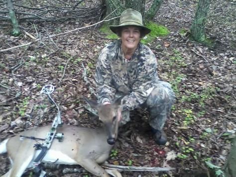 A woman bowhunter poses with a doe white-tailed deer taken with archery equipment in the Virginia hardwoods.