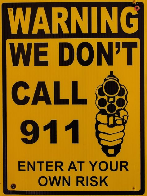 The Sign Says Warning We Don't Call 911 Enter At Your Own Risk. With Graphic of Revolver in the Hand