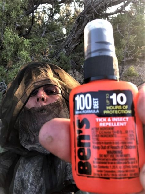 A hunter poses with a bottle of 100% Deet Insect Repellent, While bowhunting For Elk in Colorado