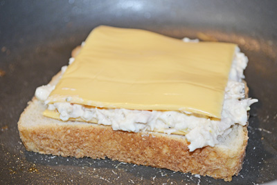 Bread side down in frying pan. Layered - cheese, tuna salad, cheese.