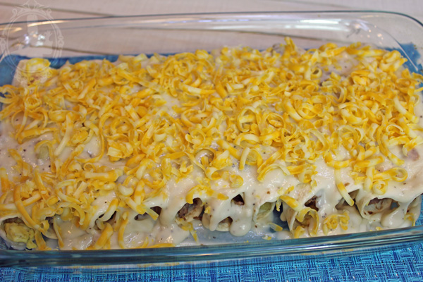 Shredded cheese sprinkled over the gravy on top of the enchiladas.