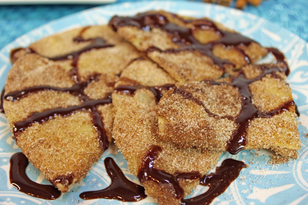 Close up of sopapillas on a plate with chocolate syrup drizzled on top.
