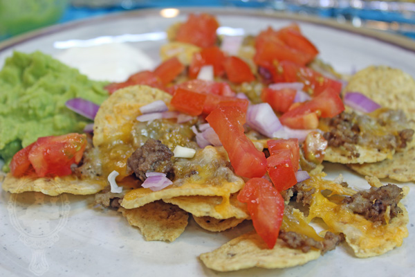 Plate of sheetpan beef nachos with nacho toppings like onions, tomatoes, sour cream and guacamole.