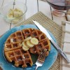 Overhead view of cinnamon sugar waffles on a blue plate with a bowl of sliced bananas and syrup in the background.