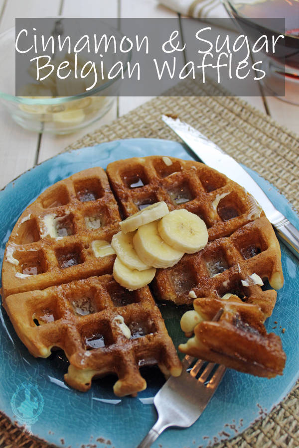 A waffle on a blue plate with a bite on a fork, ready to eat. A few slices of bananas are on top of the waffle.