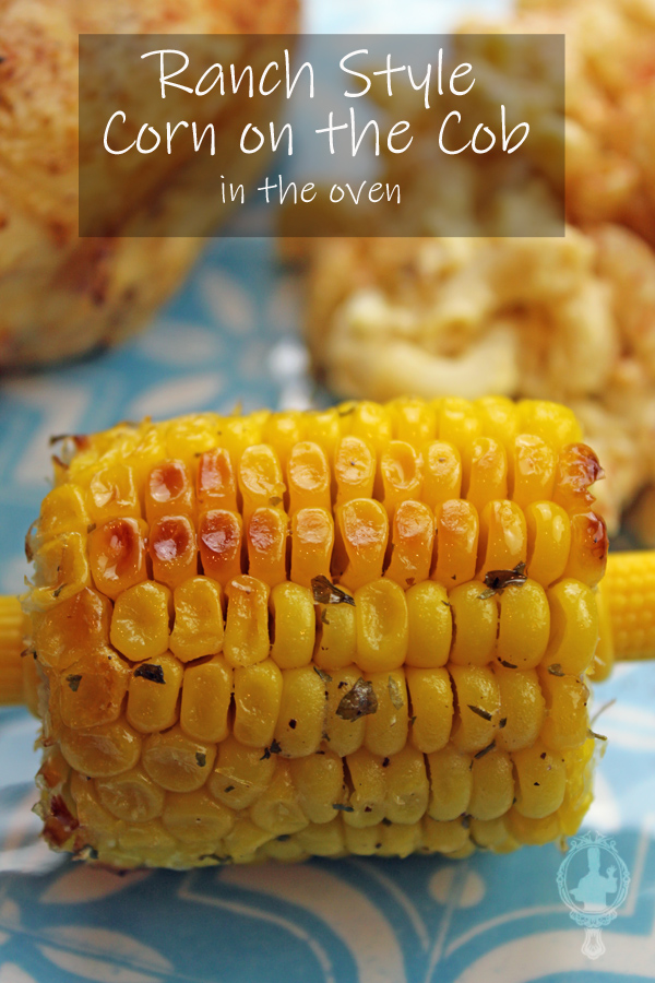 Close up picture of a corn on the cob, ranch style, with macaroni salad and grilled chicken in the background.