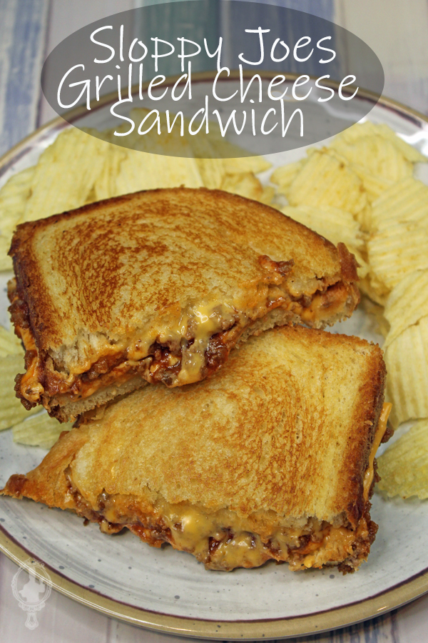 Two halves of Sloppy Joe Grilled Cheese with potato chips on a plate.