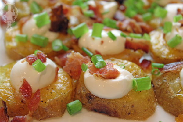 Sliced potatoes with sour cream, bacon, and green onions on top, ready to serve.