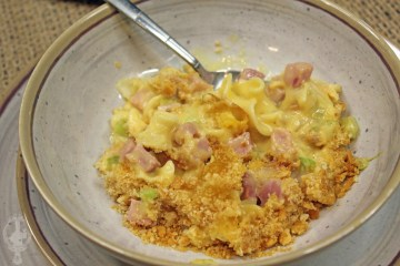 Close up of ham and noodle casserole in a bowl with a spoon.