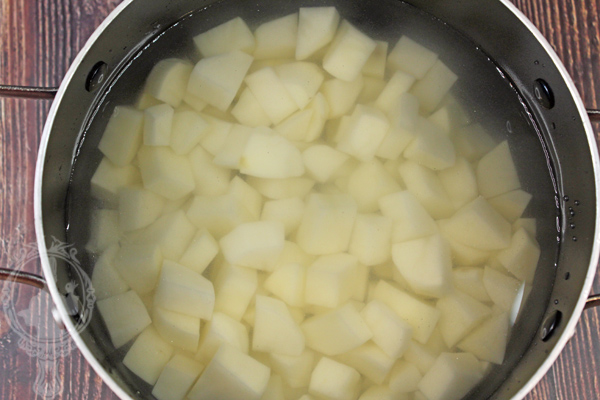 Cut potatoes in water in pot.
