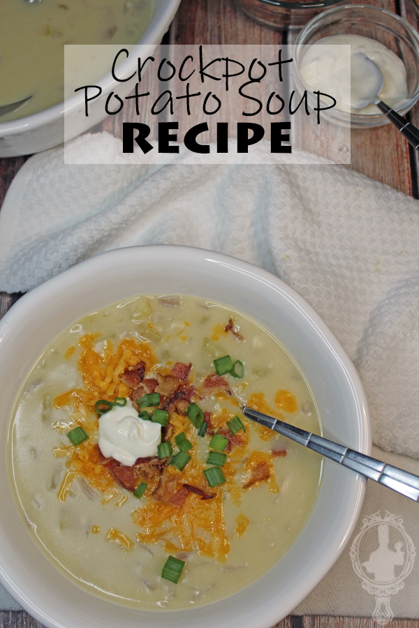 A white bowl with crockpot potato soup and a spoon in it.