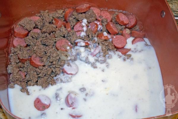 Adding hamburger/sausage mixture and gravy to bigger pan.