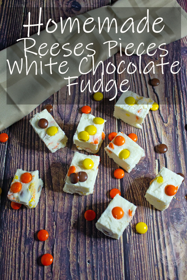 Overhead view of Reeses Pieces White Chocolate Fudge with extra Reeses Pieces laying around.