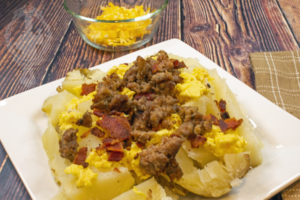 Baked potato with scrambled eggs, sausage, and bacon on top.