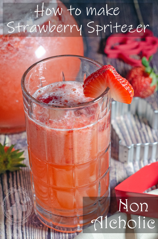 A tall glass of Strawberry Spritezer with the pitcher of it in the background.