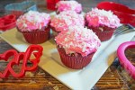 Direct view of 5 valentines day coconut cupcakes with pink icing and coconut sprinkled on top.
