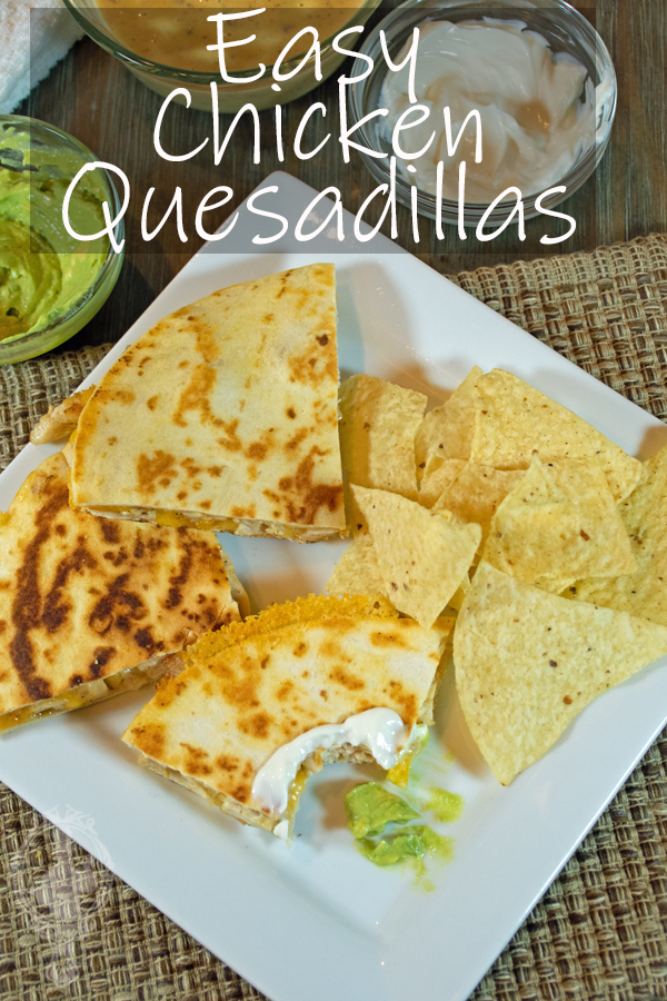 Ovehead view of chicken quesadillas, one missing a bite with quacamole and sour cream on it. On the side, some chips.