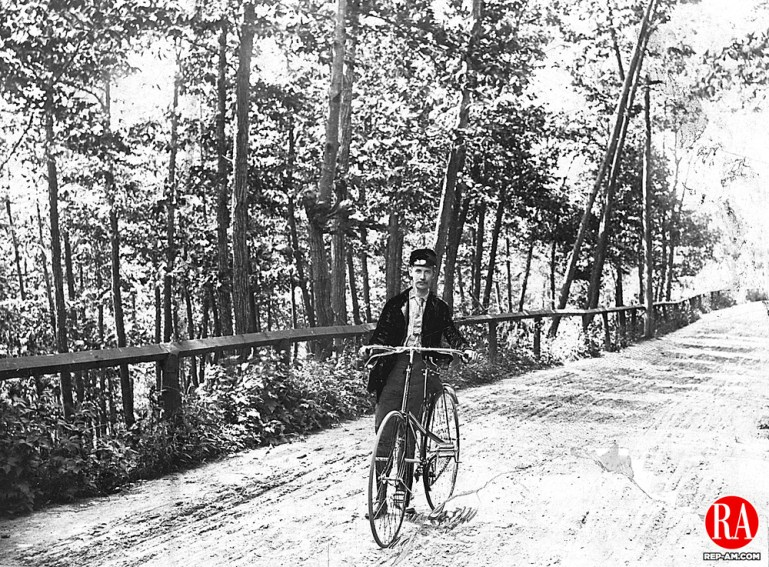 Frederick Stone, local photographer, with his bicycle on Riverside Drive, located on the west bank of the Naugatuck River, running from West Main Street to Bank Street in Waterbury, 1888.