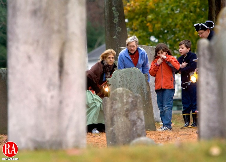 October 28, 2006 - WOODBURY - Mindy Belcher, left, portraying Mrs. Seth Preston, reads the gravestone of Seth Preston, a Woodbury resident who died in 1777, to Rosemary Maloney of Woodbury and her grandchildren Elizabeth Maloney, 9, and Thomas Maloney, 7, both of Torrington, during the annual Gelbe House