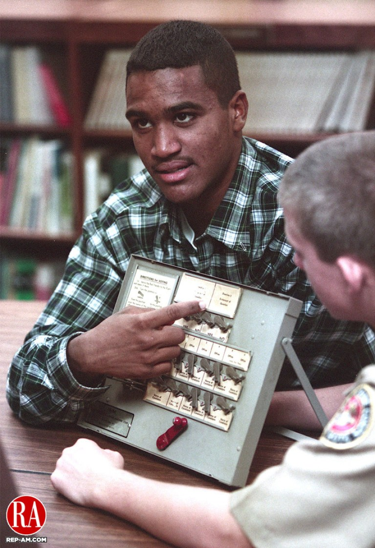 WATERBURY - 11/02/98 - Junior Vladimir Mariano explains how to work a voting machine to fellow students at Wilby High School during a mock election at the school Monday. Over 400 students were expected to take part in the 3rd annual mock election at the school, held by the history department. Photo by John Harvey Republican-American
