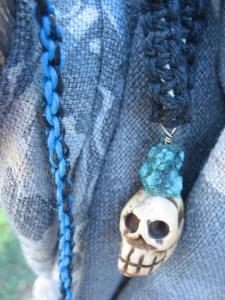 Necklace with pendant of skull carved from smoked yak bone and turquoise.