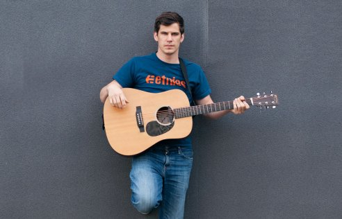Photo of singer-songwriter Isaac Grinsdale holding an acoustic guitar