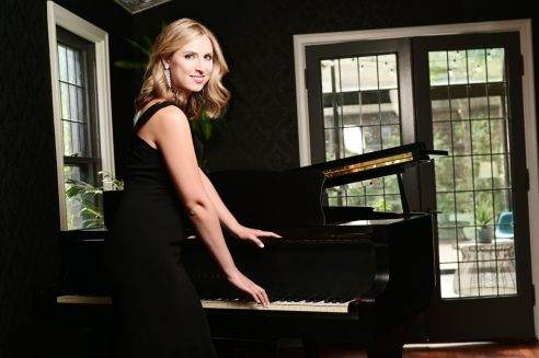 Image of blonde woman in black clothing standing in front of black piano