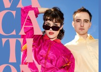 """Man and woman in pink and beige clothing against light blue background with super imposed large pink text that reads """"Vacations"""""""