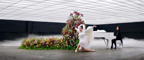 Image of man playing white piano; large sprawl of multi-colored flowers to the left of piano; dancer in white angel costume dancing in front.