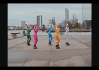 Still shot of four women wearing roller skates, each wearing different colored full body suits. City landscape in background