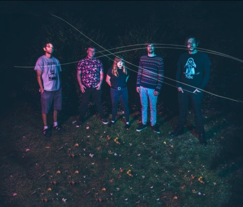 Group photo of the band, Tin Can Collective. Five people standing side by side in a dark setting.
