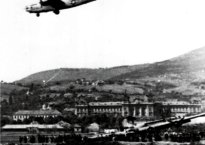 Black and white photo of a World War II era plane, descending over a town that looks to be likely based in Europe.