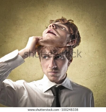 Young businessman taking off a mask - stock photo
