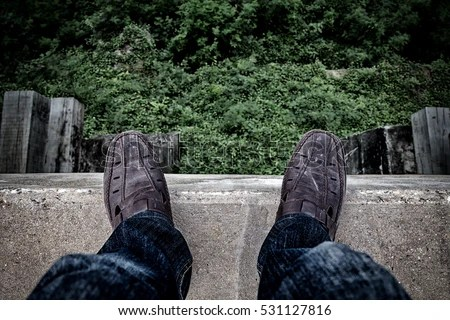 Suicide concept., Depressed young man looking down at his shoe and contemplating suicide., On the edge of a high bridge with forest below.