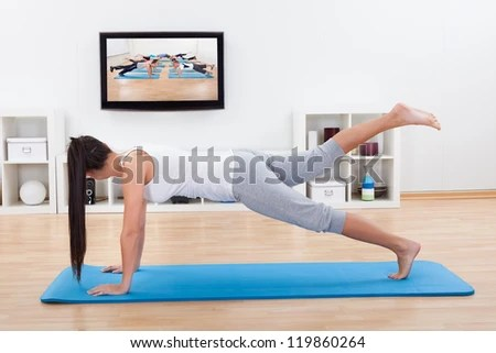 Woman practicing yoga at home standing on a mat on her living room floor while watching and participating in a class - stock photo