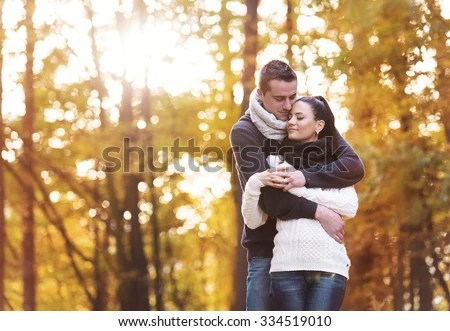 Beautiful couple in love on a walk in autumn forest - stock photo
