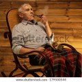 Senior man with smoking pipe sitting on rocking chair in homely wooden