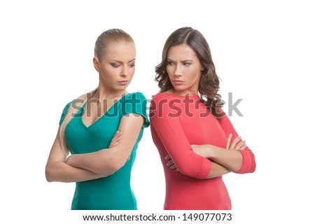 Two angry women. Two angry women looking at each other over shoulder and holding their arms crossed while isolated on white