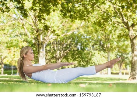 Side view of beautiful woman doing yoga in a park lying on a lawn - stock photo
