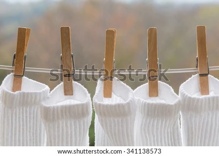 Several wooden clothespins holding a white white athletic socks on an outdoor laundry line. - stock photo