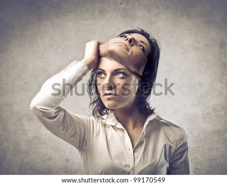 Young woman putting off a mask - stock photo