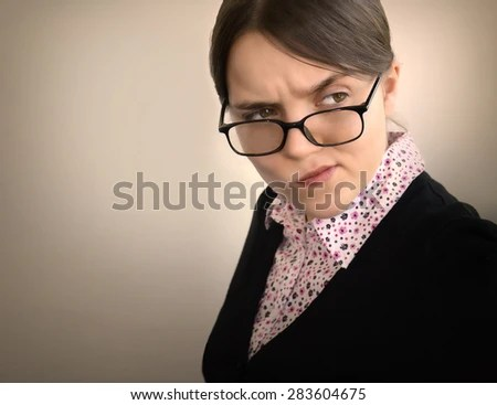 Displeased unsure arguable suspicious thinking young beautiful lady in glasses frowning wondering uncertain gaze with hostility mistrust on grey background. Negative face expression emotion perception - stock photo