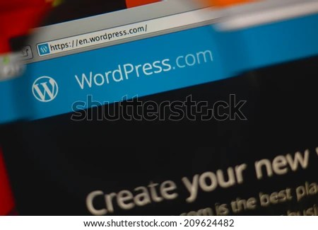 LISBON, PORTUGAL - MARCH 10, 2014: Photo of WordPress.com homepage on a monitor screen through a magnifying glass. - stock photo
